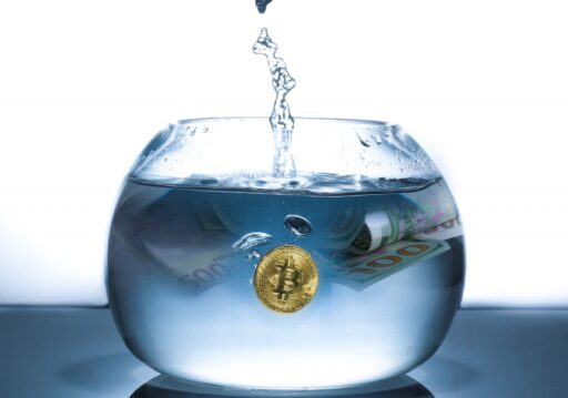 A bitcoin coin and $100 currency in a bowl being filled with water